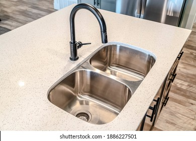 Black curved faucet over stainless steel undermount sink with double basins