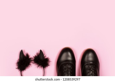 Black cute small horns with dark fur closed to black new shoes isolated on the pink background. Halloween festive concept.