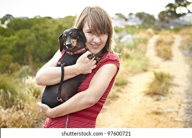 Black Dachshund dog being hugged by young lady dressed in short red summer shirt