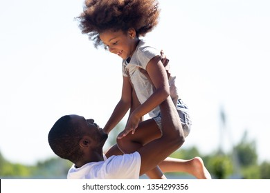 Black dad lifting daughter up having fun outdoor loving father little kid play funny game spend summer day feels happy enjoy time together, family leisure activities, relative people love care concept