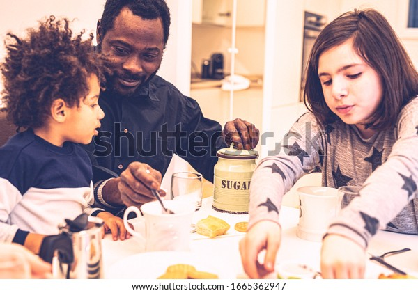 black daddy at the table with mixed race children have breakfast, daddy helps the child by pouring sugar into his cup of milk, grain and vintage filter effect by artistic choise