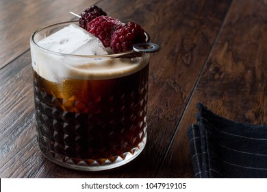 Black / Dark Beer Cocktail with Blackberries and Ice on Wooden Surface.