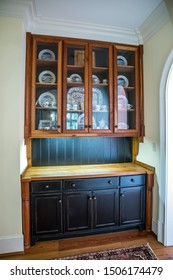 black and dark stained wood cabinet with glass doors to store china and dishes