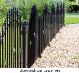 Black decorative metal fence, angular iron rods and curved upper part.