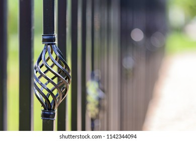 Black decorative metal fence, angular iron rods and curved upper part. Close-up of the decoration on the side.