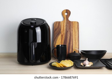 a black deep fryer or oil free fryer appliance, mug, dish and wooden tray are on the wooden table in the kitchen with a small plant in the pot ( air fryer )
