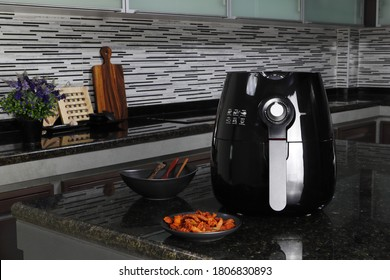 a black deep fryer or oil free fryer , air fryer appliance, and a dish of fried black pepper meat and pork are on the black marble table in the nice kitchen