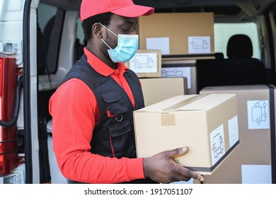Black delivery man wearing safety mask for coronavirus prevention - Focus on face