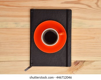 Black diary and cup of coffee on wooden table, top view