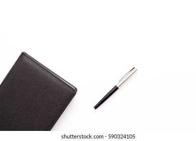 black diary and pen on a white background. business minimal concept. Top view. Flat lay