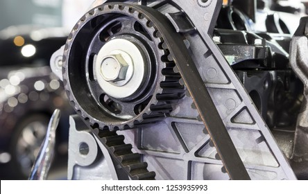 Black diesel engine timing belt that synchronizes the rotation of the crankshaft and the camshafts by controlling open and close of valve ; close up ; industrial background