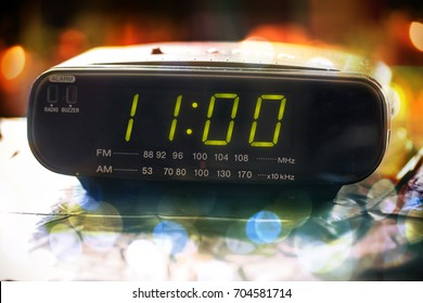 Black digital alarm radio clock.Alarm radio clock indicating time to wake up.Digital clock closeup displaying 11:00 o'clock.Digital radio clock displaying 11:00  on bokeh background