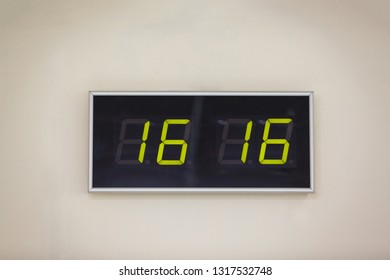 Black digital clock on a white background showing time sixteen hours sixteen minutes
