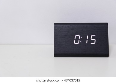 Black digital clock on a white background showing time 00:15 (fifteen minutes)
