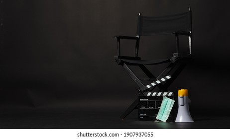Black Director chair ,face mask and clapper board or Clapperboard or movie slate with megaphone .it use in video production or film and cinema industry. It's put on black blackground.