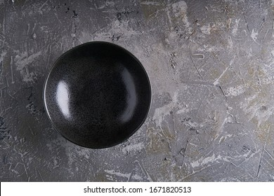 Black dishes on a gray background Vertcal Copy space Dark photo