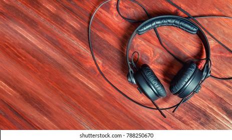 Black DJ headphones on a wooden table.