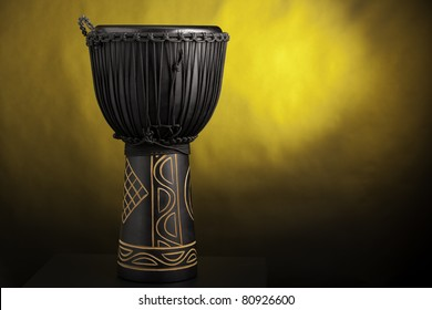 A black djembe conga drum isolated against a yellow spotlight background.