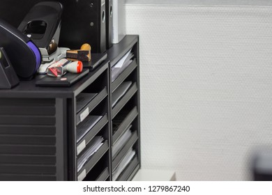 black document tray with papers and hole puncher and stamp