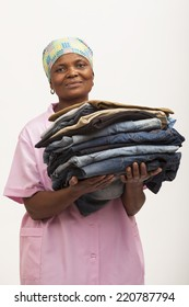 Black domestic worker holding laundry