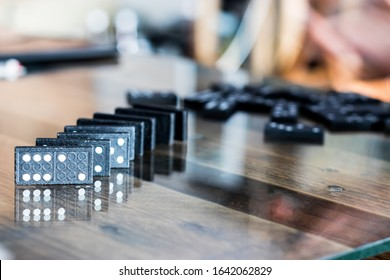 The black Domino Game, made of wood, is placed on a glass-covered wooden table on top.