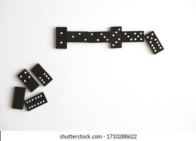 Black dominoes lie in line on white background, top view. Board game. Place for text