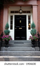 Black door in Boston on a stately brownstone in the beacon hill area. Ornate flower urns and elaborate door knocker. Lights on inside the house can be seen from the street.