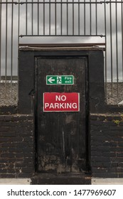 """Black door with """"No Parking"""" and """"Fire Exit"""" signs"""