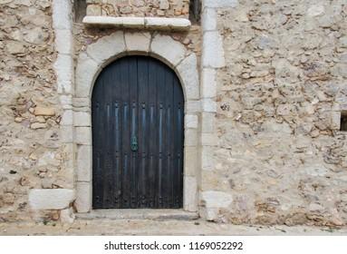 Black door on stone wall