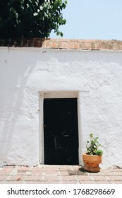 Black doorway in the wall of old white adobe plaster adobe house home with potted plant and tree roof tiles minimalist southern Spain Mediterranean Architecture