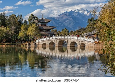 Black Dragon Pool to the Five Phoenix Tower and the Five Holes Bridge. In the background is Jade Dragon Snow Mountain. The Old Town of Lijiang is located in Lijiang City, Yunnan, China.