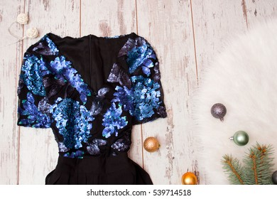 Black dress with blue sequins on a wooden background, Christmas balls on white fur. Fashionable concept, top view