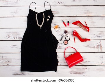 Black dress and fashion accessories. Red handbag clutch and heels, black short dress, cosmetics, vintage wooden background.