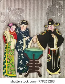Black dress man hold the woman hand in Chinese traditional opera characteristic stucco on the wall.