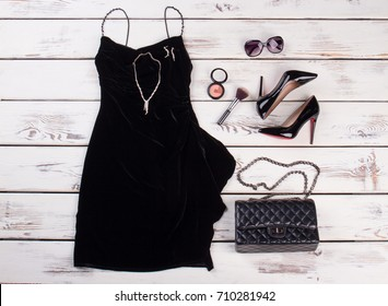Black dress and stylish accessories. Beautiful lady garment on light wooden background.