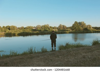 Black dressed angler fishing at the Hunte river at sunset, seen in Oldenburg, historic town in Lower Saxony, Germany, copy space for text, concept of nature, solitude, tranquility
