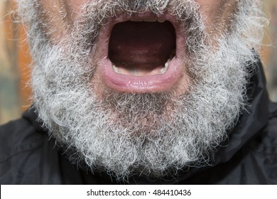 black dressed elder man with a grey full beard and open mouth, concept for religious preachment and the power or danger of words