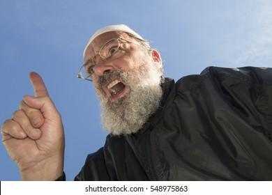 black dressed elder muslim with beard and takke speaking with raised trigger finger