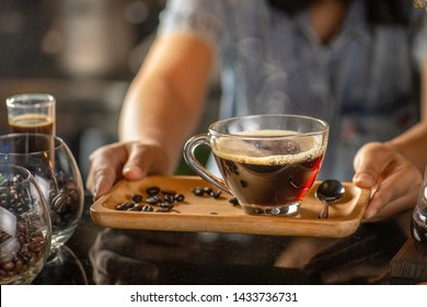 black drip coffee in glass cup, Barista making drip coffee by pouring spills hot water on coffee bean. Barista serve holding cup of hot black coffee or americano for serve on wooden table cafe shop