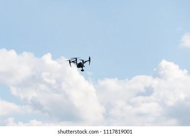 Black Drone camera flying in clouds blue heaven sun