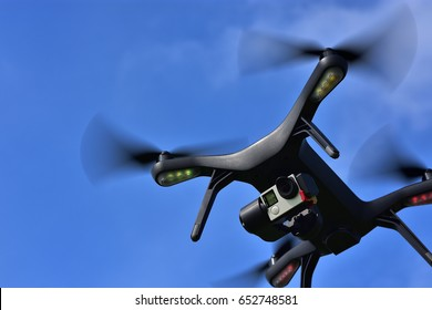 Black drone quadcopter with camera flying over blue sky. Angle view, copy space.