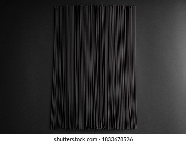 Black dry raw noodles spaghetti on dark background