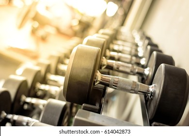 Black dumbbell set. Close up many metal dumbbells on rack in sport fitness center , Weight Training Equipment concept.