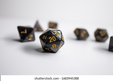 Black Dungeons and Dragons dice set. The D20 dice is the most prominent at the front of the rest of the dice. The black contrasts greatly with the stark white back drop the dice were shot on.