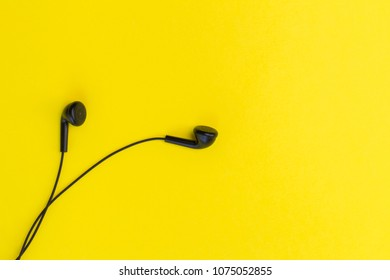 Black earphones on the yellow background. Listening to music concept. Top view, copy space, flat lay