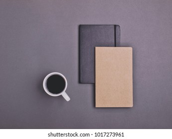 Black and eco brown notebooks and black coffee isolated on dark gray background. Copy space. Flat lay.