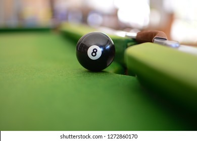 The black eight ball sitting on the edge of the pocket about to fall in. Nearly at the end of playing a game of pool.