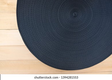 Black elastic band in reel on wooden background. Top view. The linen gum, elastic polyester band is used for clothing.