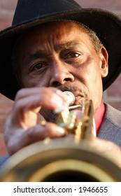 Black elderly man playing an old trumpet.