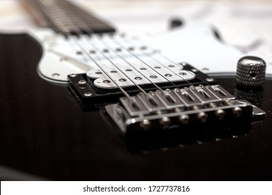 Black electric guitar bridge and stings in closeup